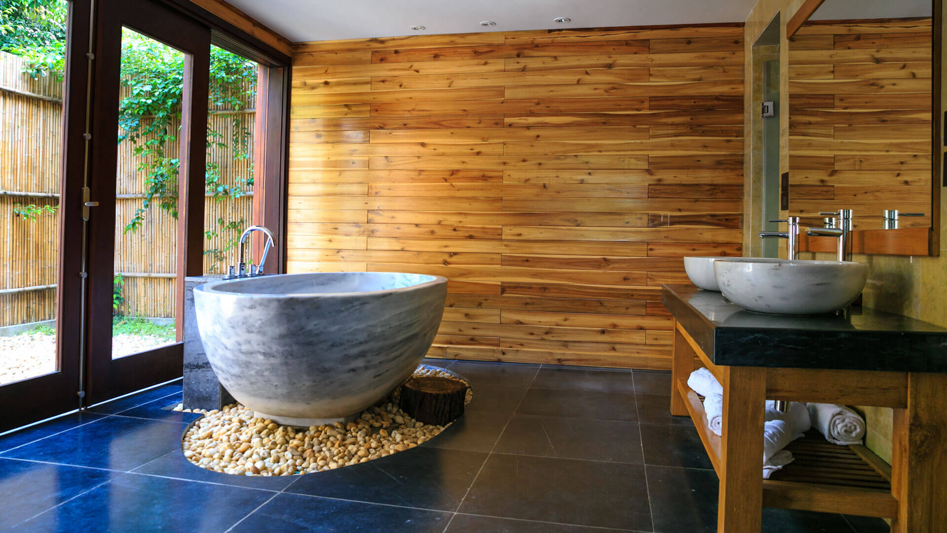 Modernes Bad mit großformatigen Fliesen und Natursteinbadewanne