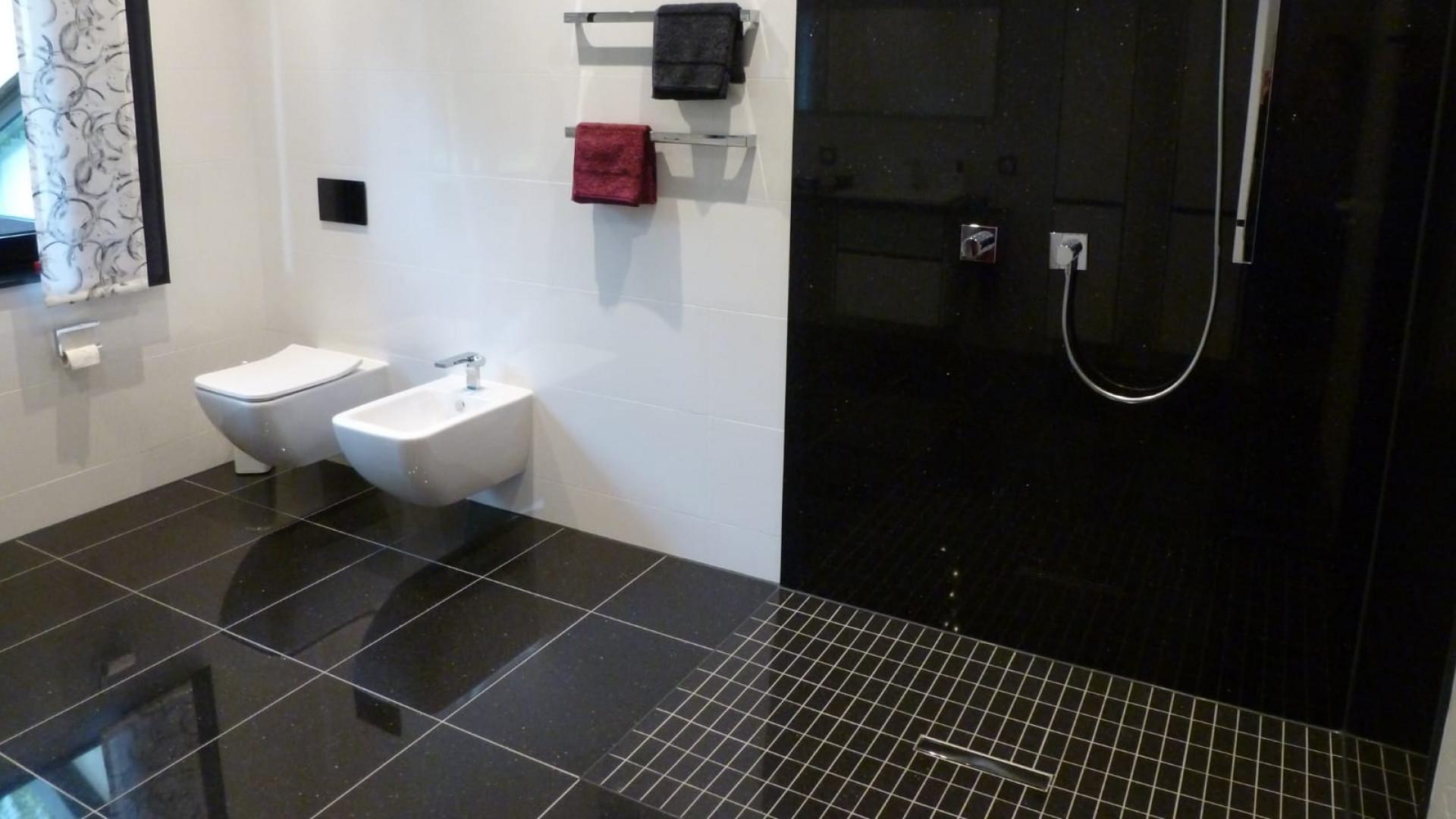 Minimalistisches Badezimmer mit kontrastreichen großformatigen Fliesen